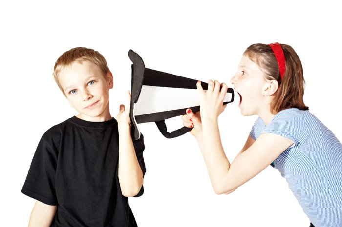 A humourous portrait of a little girl with a megaphone shouts in the boy's ear.