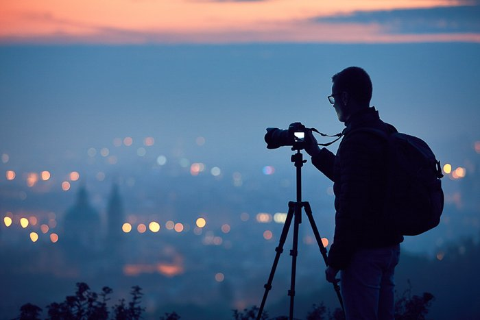 silhouette of photographer on a hill with camera on tripod taking a photo of a city at dusk