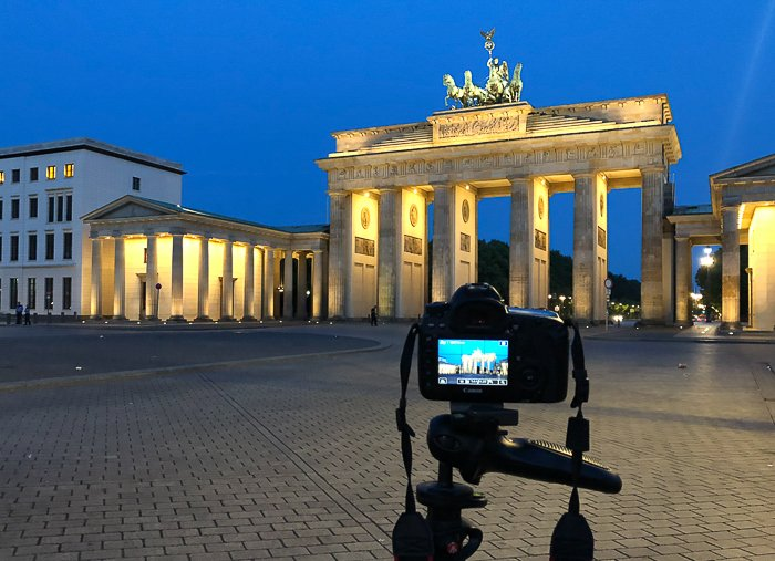 A DSLR camera on a tripod photographing the Brandenburg Gate in Berlin at night