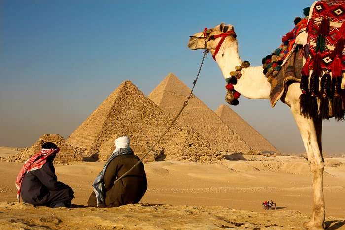 two bedouins resting on the desert sand looking at the pyramids in Egypt while their camel waits