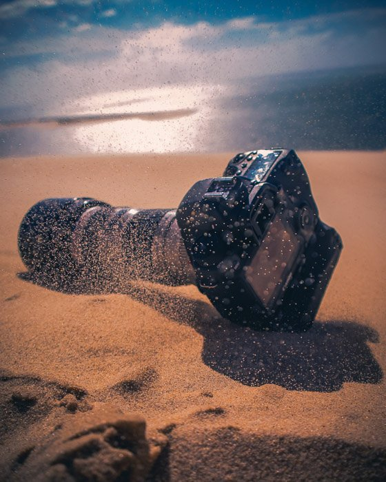 A DSLR camera resting in the sand at the beach