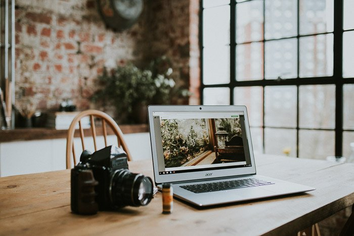 A DSLR camera and laptop on a wooden table
