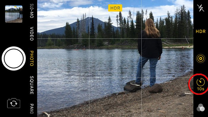 Screenshot of using the iphones self timer to take a photo of a girl standing by a lake