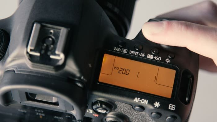 A close up of a DSLR camera showing the ISO value