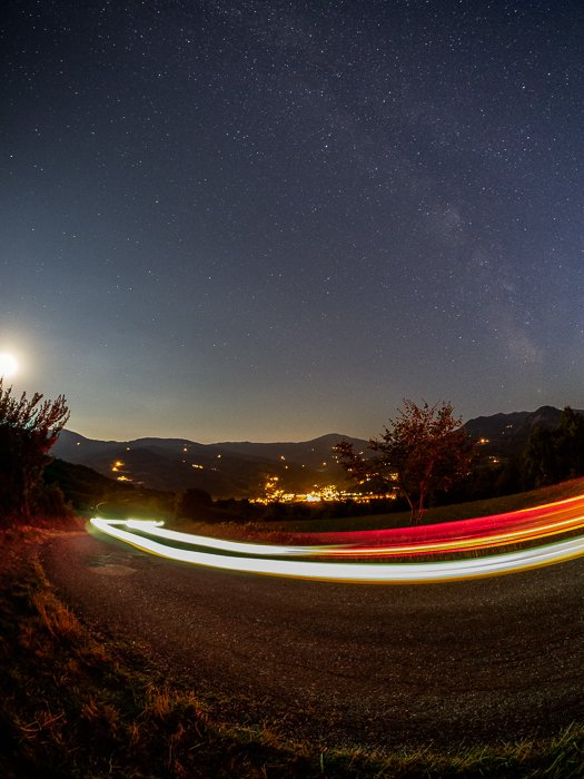 A nocturnal landscape including light trails from my car running on the road in front of me.