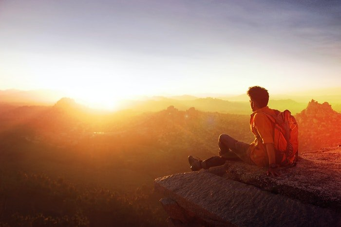 Man sitting looking out at mountains during sunset