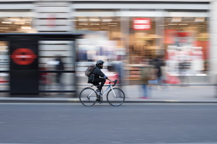 A cyclist riding down a roadway with blurry background behind