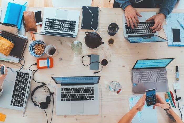 Overhead shot of 5 laptops on a messy office desk