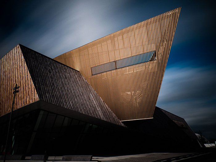 The Congress Center in Mons (Belgium). Red brown Geometric structure in contrast against a darker blue sky