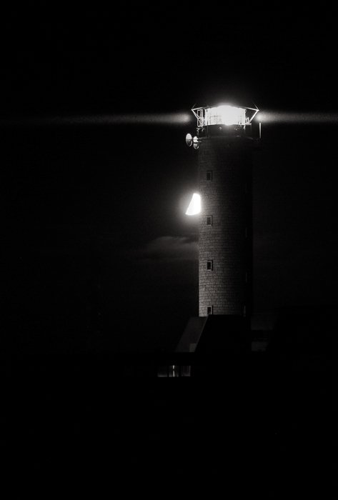 black and white photo of The moon behind the lighthouse in Cap-Gris-Nez against a black night sky
