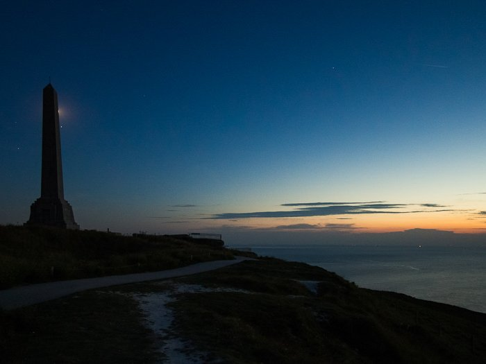 silhouette of the Obelisk in Cap-Blanc-Nez in France, against a dark sky at dusk, the sunset fading in the horizon