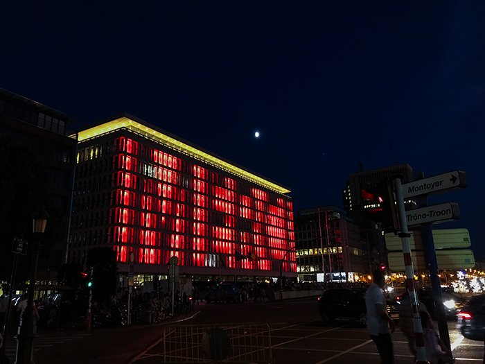 Photo of a rectangular building with lots of windows at night, with changing lights on its face