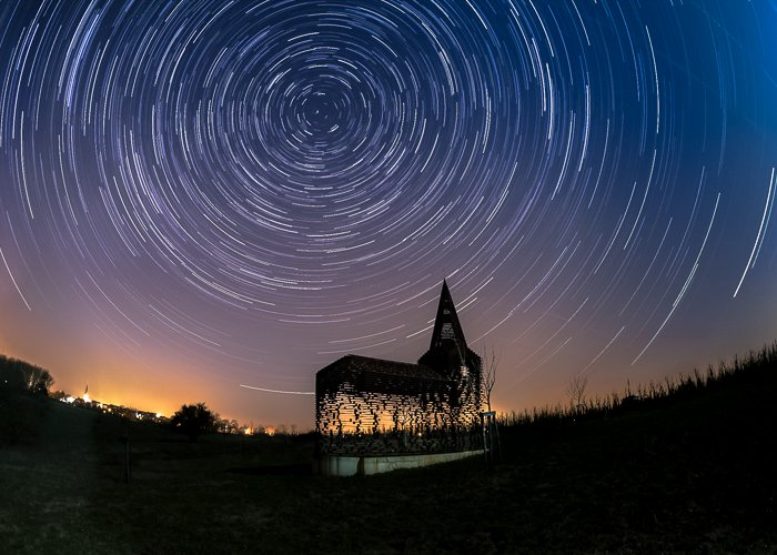 silhouette of the See Through Church lit warmly from behind, beneath a star trail and an orange blue dusk