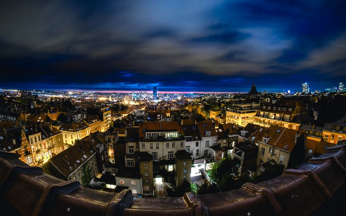 suburban city townscape lit by yellow lights, an electric blue horizon against a cloudy night sky