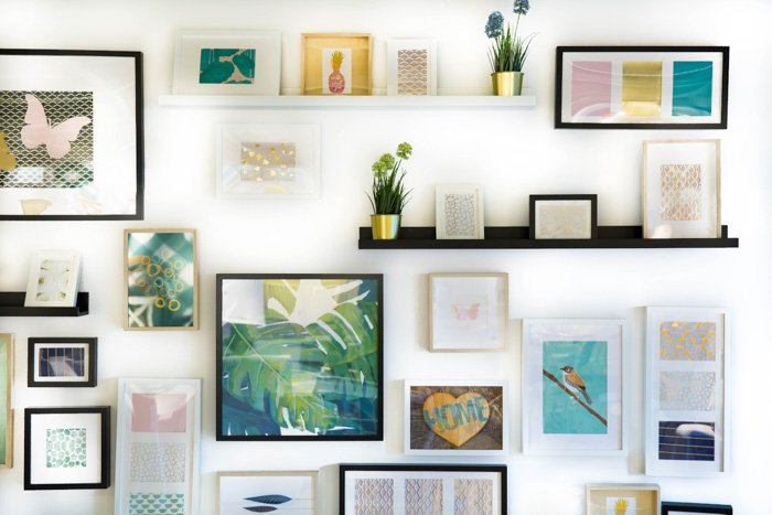 Bright and airy interior photography of different sized picture frames on a white wall