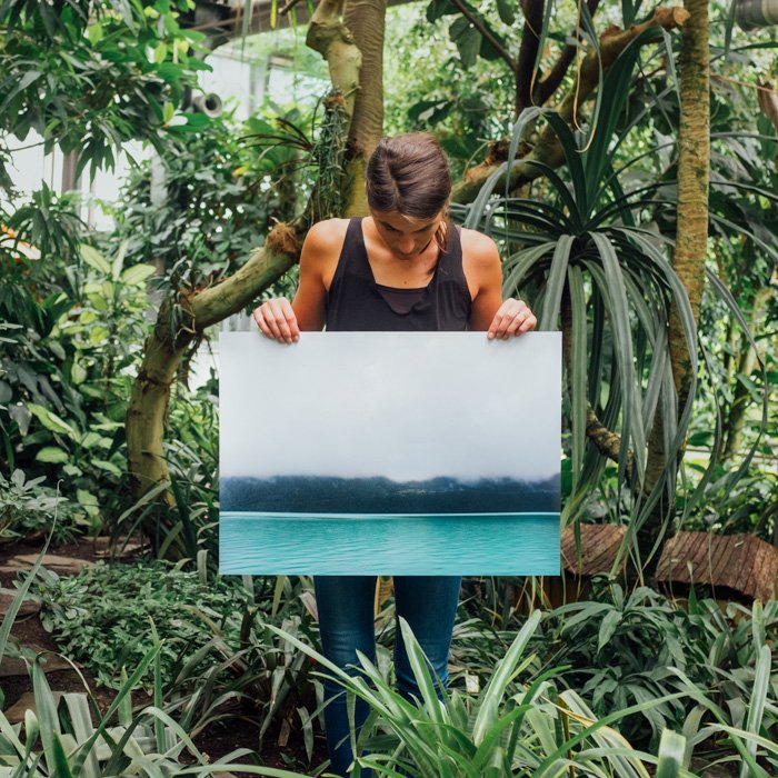 A woman standing in a tropical forest setting holding up a large sized photo print