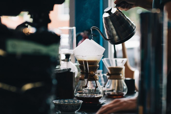 A barista pouring coffee into a v60 filter at a busy cafe