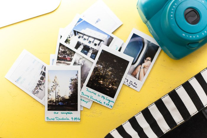 A pile of photos from an instant camera on a yellow surface