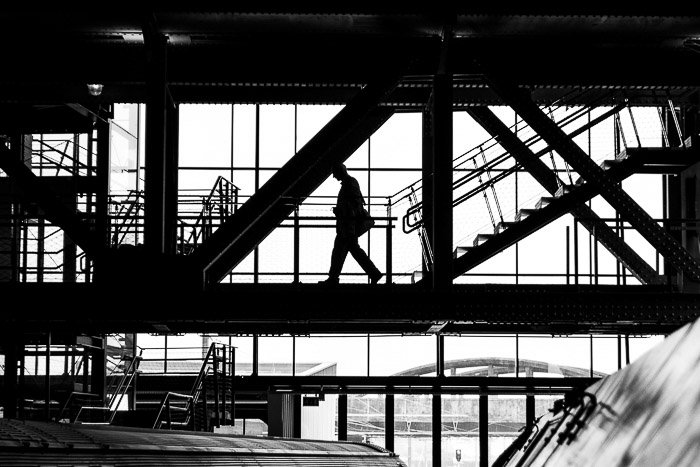 Black and white street photo of a man's silhouette against some windows.