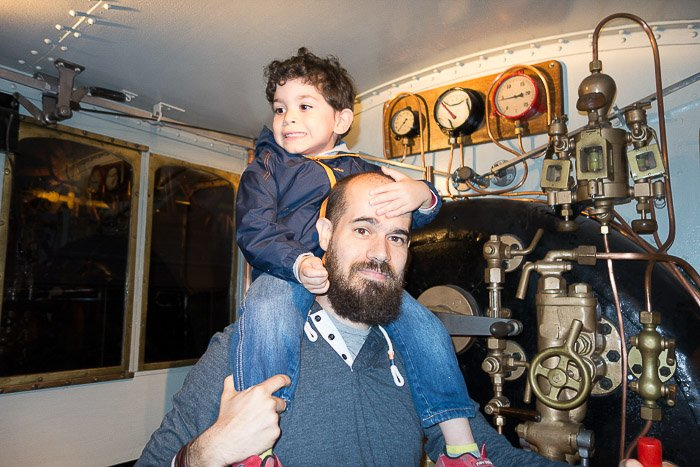 A father and son visiting a train museum