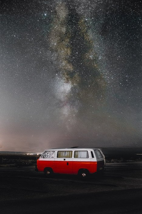 Striking shot of the milky way at night over a red van