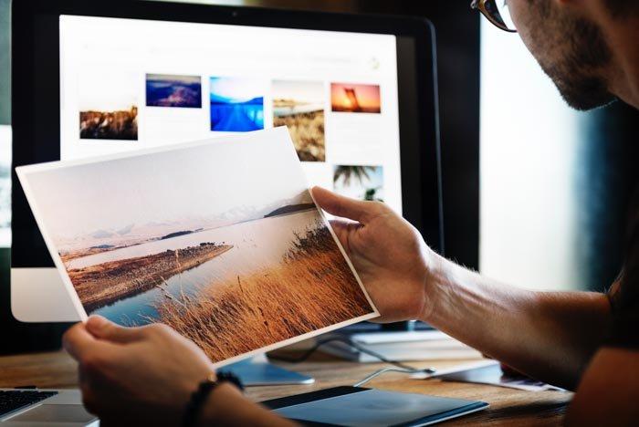 A close up of a man holding a landscape print
