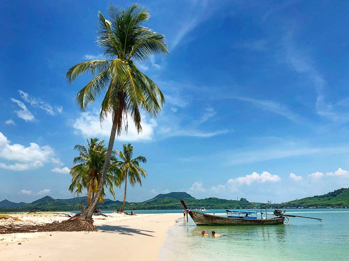 A dreamy tropical beach scene with palm trees and wooden boat