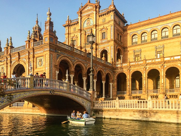 Bright travel photography of people in a boat on a canal in front of a beautiful building