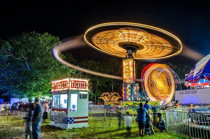 A stunning night photography shot of an amusement park demonstrating shutter speed uses