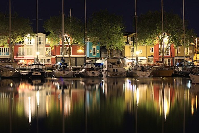 A stunning night photography shot of boats in a harbour with a beautiful pattern reflected in the water
