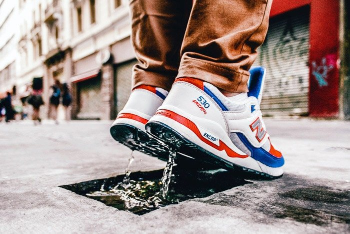 Close up photo of a person wearing trainers jumping in a small puddle on the street using a fast shutter speed