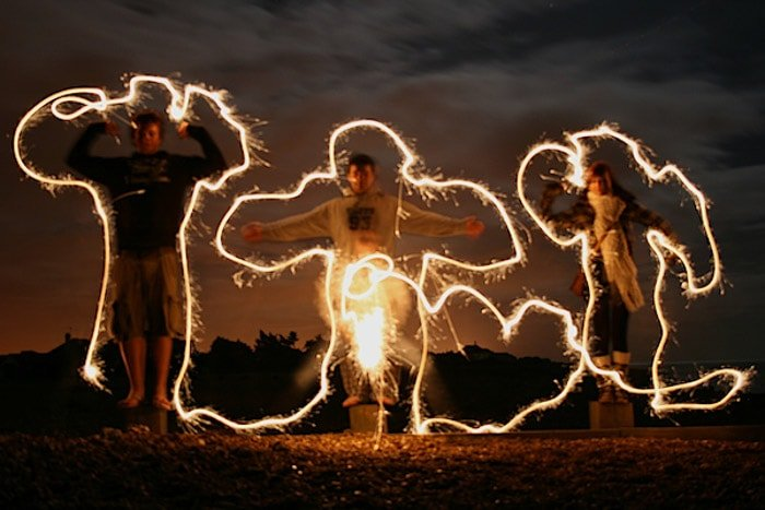 Three people surrounded by lighting painting at night