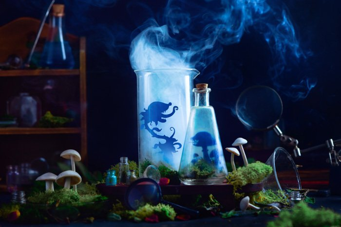 Mystical still life featuring glass bottles with the silhouettes of tiny cut out characters inside and smoke billowing out