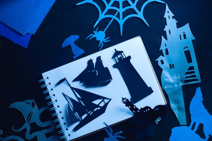 A variety of papercut silhouettes on a white notebook page