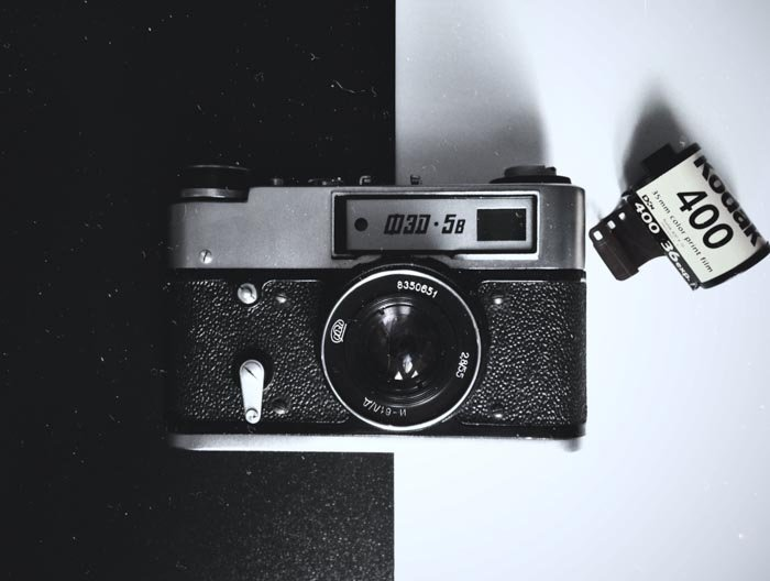 An overhead shot of an old film camera on black and white background with a roll of film beside it - using film for street photography