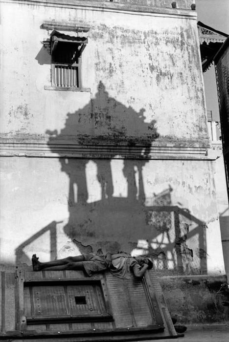 a henri cartier-bresson photo of a man lying outside a building