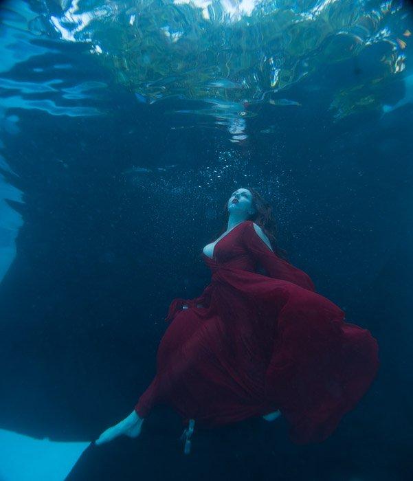 A beautiful woman in flowing red dress posing underwater