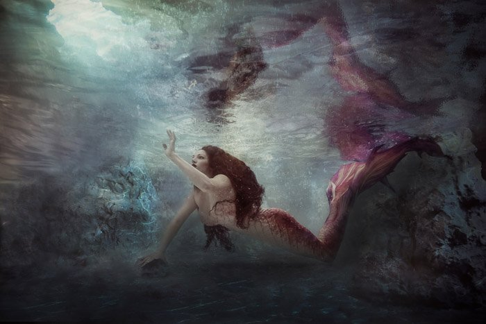 Beautiful and mystical underwater photography shot of a mermaid girl swimming underwater