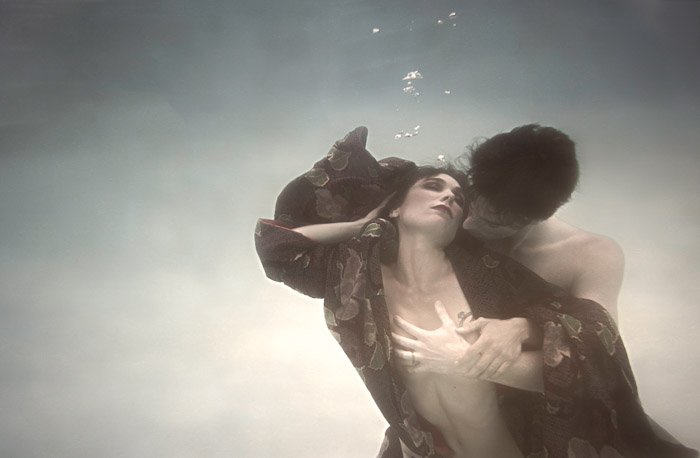 atmospheric shot of a couple in a passionate embrace underwater