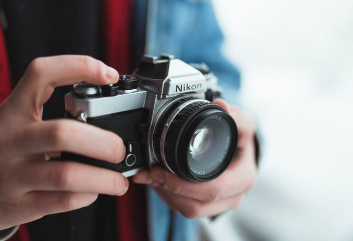 Close up of a persons hands hold a Nikon camera