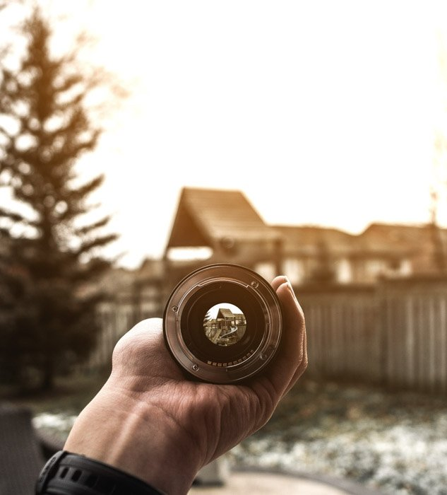 Close up of a persons hand holding a camera lens over a building