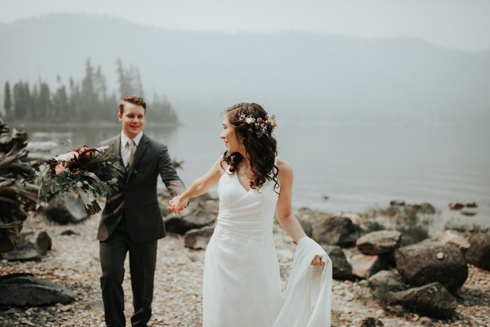 A beautiful wedding portrait of a newlywed couple holding hands on a beach