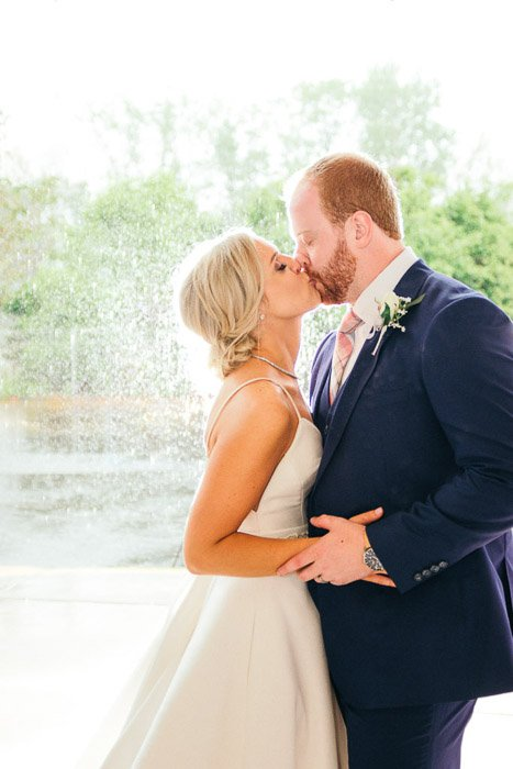 A wedding portrait of the bride and groom kissing outdoors in front of a fountain