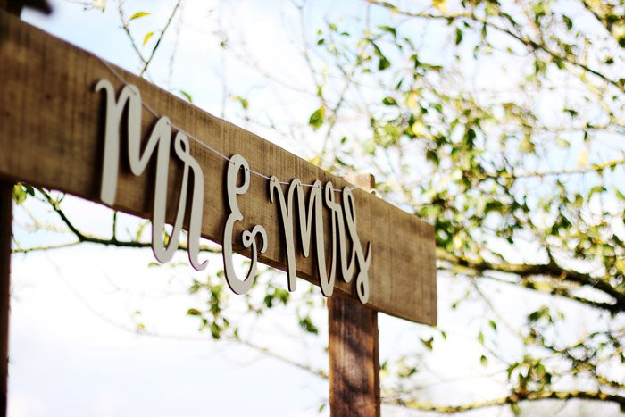 A closeup shot of a wooden signpost with the words 'Mr and Mrs'