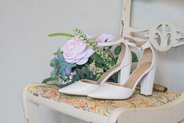 Still life of a pair of bridal shoes and a bouquet on a chair