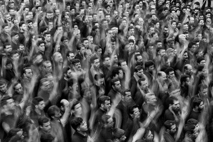 An overhead black and white photo of a crowd of people with their hands raised in the air