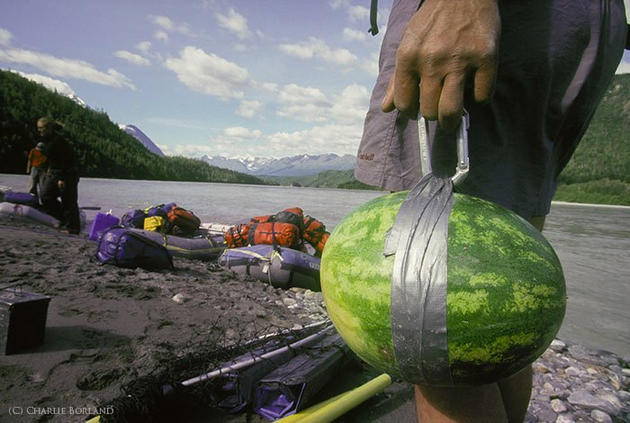 close up of a man's hand carrying a watermelon, travellers gear and the short of a lake in the background