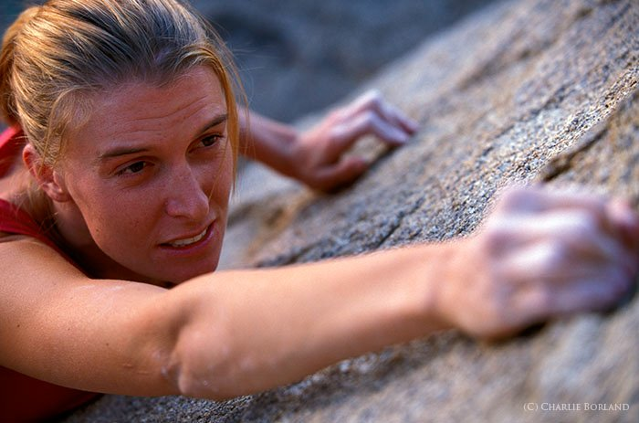 close up of a woman in a red shirt climbing a mountain face