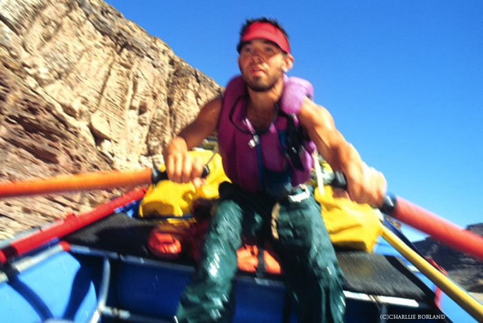 close up of a man in a blue boat rowing the river on an adventure photography trip, the mountain behind him