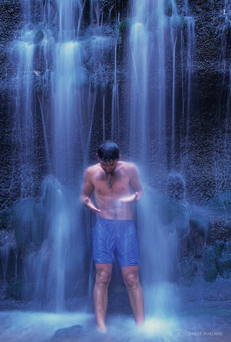 man standing in the shower of a waterfall
